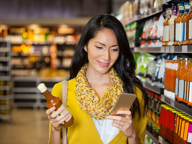loyalty technology, woman smiling at mobile phone while shopping