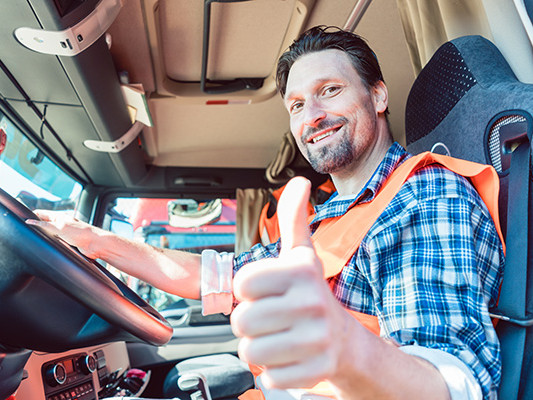 "Man looking at camera, smiling and holding a ""thumbs up"" inside a truck."
